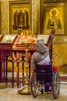A disabled woman in the church lights the candles