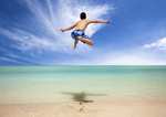 Happy young man jumping on the beach