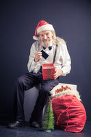 Happy office Santa holding cell phone as christmas gift.