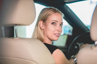 Beautiful young woman on driving seat in new car.