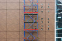 red-blue scaffolding on a background of brown panels on the wall of a shopping mall during a renovation