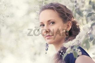 Happy beautiful fashion woman walking in a spring blooming garden
