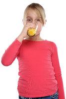 Mädchen trinken Orangensaft Orangen Saft gesunde Ernährung Hochformat Freisteller freigestellt isoliert