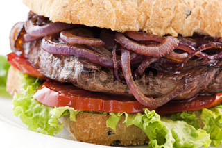 Steak burger with beefsteak, onion rings and tomotos as closeup on a white background
