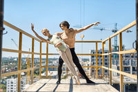Ballet dancers posing at concrete balcony