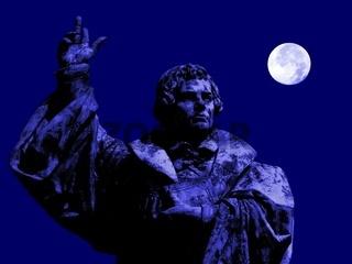 Statue Martin Luthers mit Bibel und erhobener Hand bei Vollmond