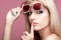 Young blonde woman with fun candy glasses on pink background  with finger on lips