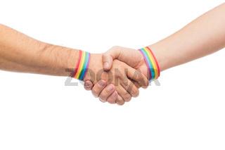 hands with gay pride wristbands make handshake