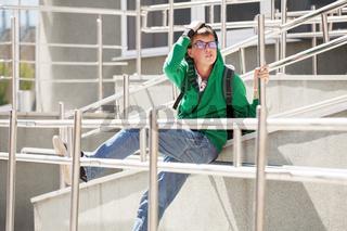 Sad teen boy in a hoodie against a school building