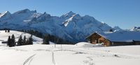 Old timber hut and snow covered mountain Range. Mountains Schlauchhorn and Oldenhorn.