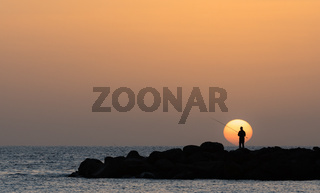 Man fishing, low sun at the Amadores beach on Gran Canaria island in Spain.