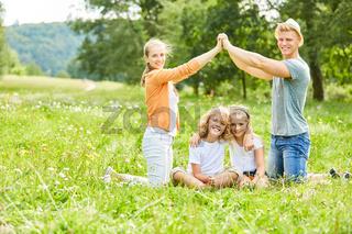 Glückliche Eltern formen Dach mit den Händen