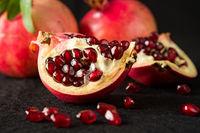 Closeup of half pomegranate fruit and seeds