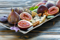 Figs,blue cheese and walnuts on a bronze tray.
