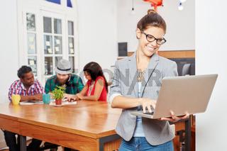 Geschäftsfrau mit Laptop vor ihrem Team