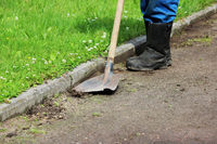 The worker removes the growing grass on a gravel path using an old shovel.