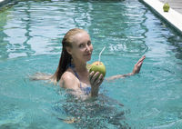 The young attractive woman with long hair in a swimwear in the pool with cocktail in coconut