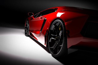 Red fast sports car in spotlight, black background. Shiny, new, luxurious.