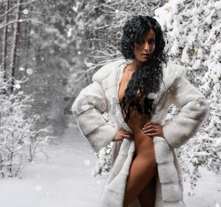 Gorgeous naked brunette wearing white fur coat posing in a snowy forest