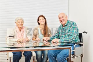 Senioren und junge Frau spielen Puzzle spielen