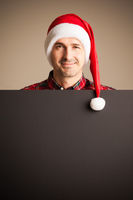 Man in santa christmas hat holding placard