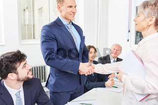 Ältere Geschäftsfrau gratuliert jungem Mann