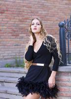 Outdoor fashion portrait of stylish lady wearing trendy black dress