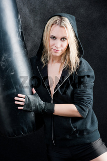 Boxing training woman in black hold punching bag