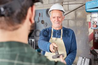 Älterer Handwerker reicht Hammer weiter