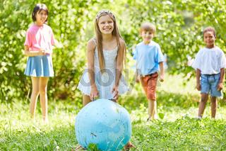 Lächelndes Mädchen mit Weltkugel