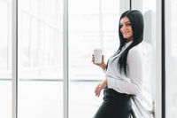 Successful confident young business woman with coffee in an office setting