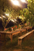 Prepared table for a rustic outdoor dinner at night with lamps