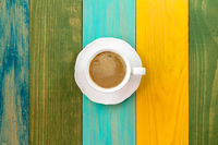Cup of cappuccino on color table