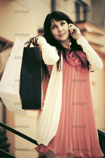 Happy woman with shopping bags calling on mobile phone outdoor