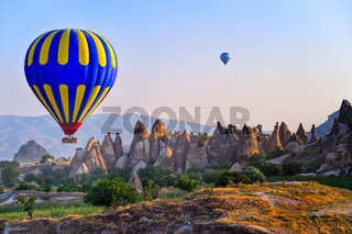 Cappadocia hot air balloon flying over bizarre rock landscape in Turkey
