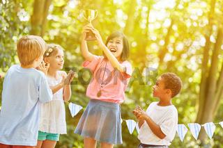Mädchen mit Pokal jubelt als Gewinner bei Siegerehrung