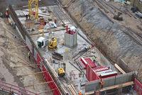 Baustelle mit Baugrube, Baumaschinen, Bauarbeitern von oben