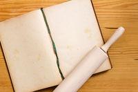 Kochbuch und Nudelholz auf Holz