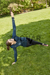 Frau auf Wiese beim Fitnesstraining