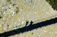 Schatten von zwei Personen auf dem trockenen Flussbett unter einer Hänegbrücke