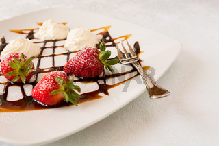 Strawberries with cream on a square plate