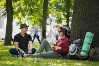 Teenagers tourists with backpacks in the park at summer midday