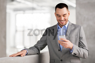 smiling businessman with smarphone at office