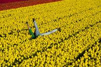 Paar vergnügt sich in einem Feld gelber Tulpen