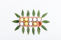 Tray with yellow eggs and green petals on a white background