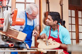 Handwerker erklärt Lehrling die Holzarbeit