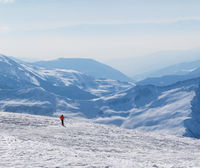 Skier downhill on snowy off-piste slope and mountains in haze