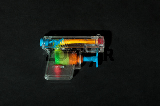 colorful water gun on black background