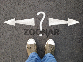 feet standing on asphalt with arrows pointing left and right with question mark