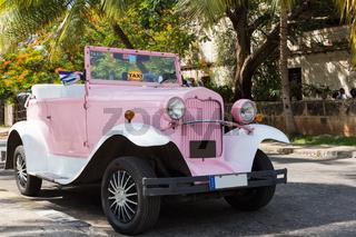 Amerikanischer rosa farbender Cabriolet  Oldtimer parkt unter Palmen in Varadero Cuba